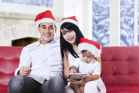 Portrait of beautiful family smiling on camera and enjoy christmas day at home photo