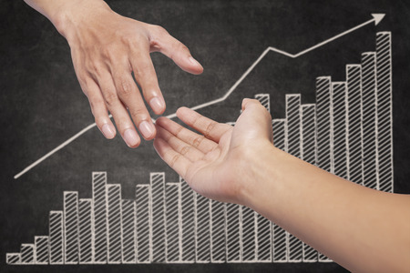 growing partnership: Helping hand with business growth graph on blackboard Stock Photo