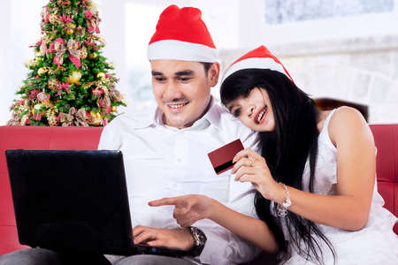 Portrait of happy couple wearing christmas hat and use credit card for shopping online with laptop photo