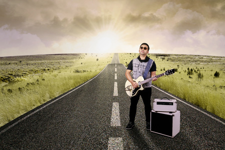 Portrait of talented guitarist playing electric guitar on the road Stock Photo