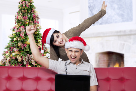 Cheerful asian couple using laptop for shopping online from home in christmas day photo