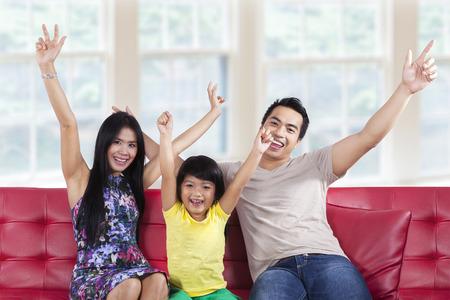 descansando: Retrato de familia asi�tica que se sienta en el sof� y expresando feliz en casa