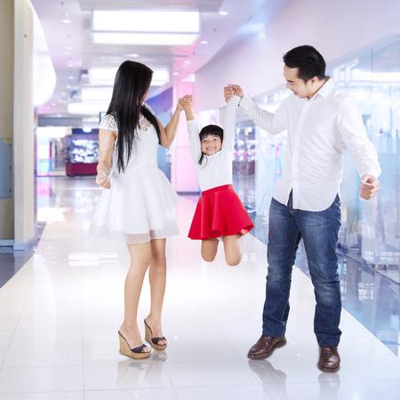 ni�os de compras: Dos padres sostener y levantar a su hija en el centro comercial