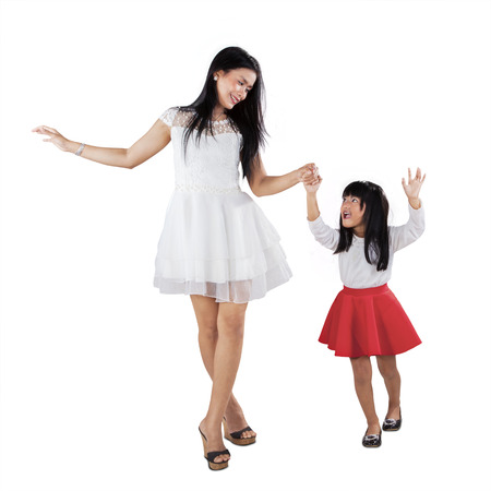 Portrait of young mother and her daughter holding hands in the studio photo