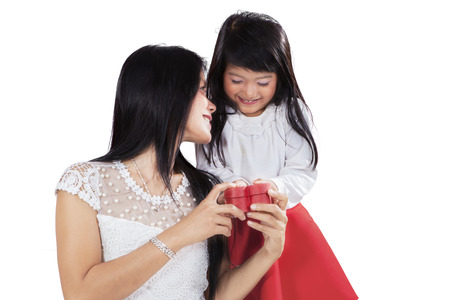 Girl giving a gift box to her mother in studio, isolated over white  photo