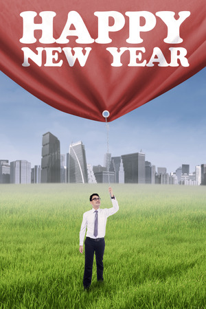 pulling rope: Portrait of asian worker pulling a big banner with new year text outdoors Stock Photo