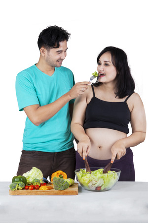 Portrait of husband giving vegetable to his pregnant wife, isolated on white photo