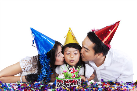 Portrait of two parents kissing their daughter when blowing candle on birthday cake photo