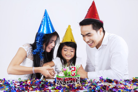 Cheerful little girl cutting a birthday cake with her parents in birthday party photo