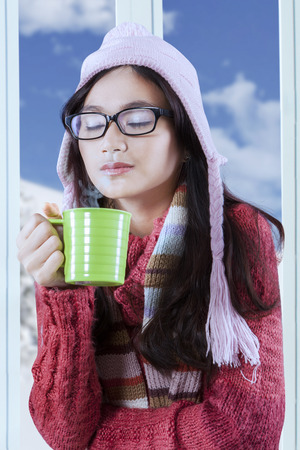 Young hispanic girl drinking hot tea while wearing warm clothes at home with winter  photo