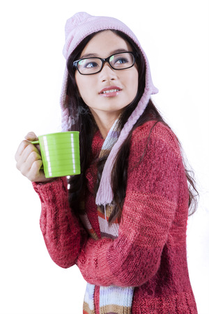 Portrait of beautiful asian girl wearing sweater and drinking hot tea, isolated over white photo