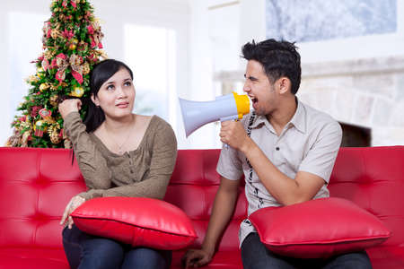 relationship problems: Portrait of rude man using a megaphone to scold his girlfriend in christmas day