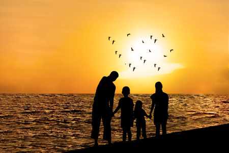 Silhouette of happy family on beach watching sunset together photo