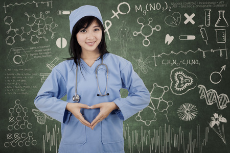 Portrait of female student with surgeon coat makes heart symbol in class photo