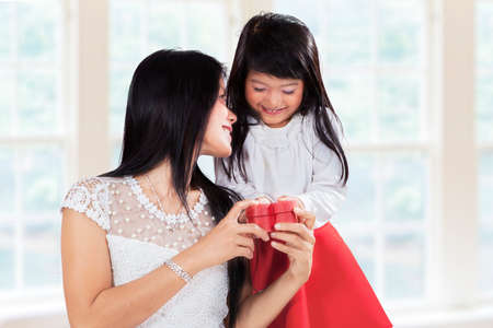 Cute little girl giving present to her mother at home, symbolizing thankful to parent photo
