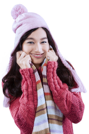 Beautiful woman wearing warm clothes and smiling at the camera in studio, isolated over white photo