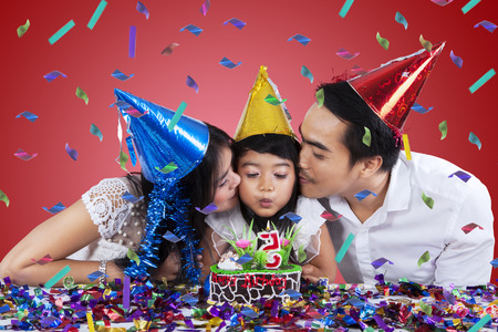 Portrait of asian parents celebrate their childs birthday and kiss the child when blowing candle photo