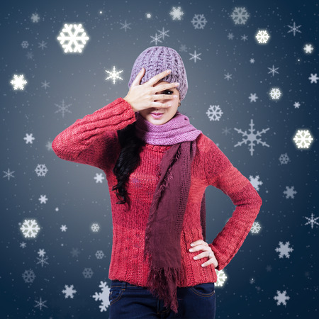 woman behind: Woman wearing knitted scarf and hat hiding behind hands on winter