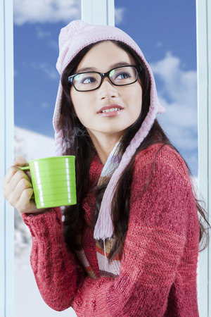 Attractive girl wearing knitted clothes enjoy hot drink with winter  photo