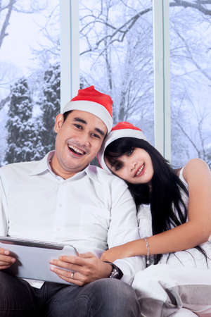Happy woman wearing christmas hat and lean on her boyfriends shoulder in winter day photo