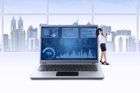 Young businesswoman typing message on phone while lean on laptop with business chart on the screen photo