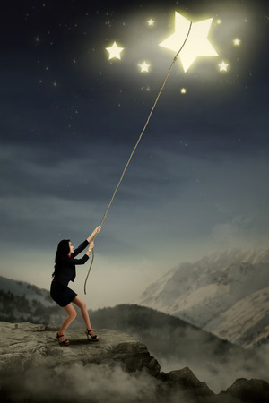 Portrait of young businesswoman taking stars from the sky spac photo