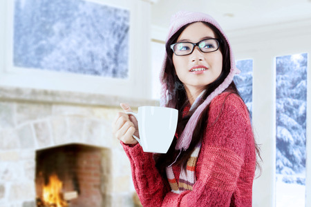 Portrait of beautiful young asian woman holding a cup of hot drink while wearing sweater and hat at home photo