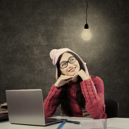 daydream: Beauty face of female student daydream, studying with laptop and books while wearing sweater and looking at bright lamp