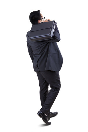 Full length of successful businessman walking in studio while carrying briefcase photo