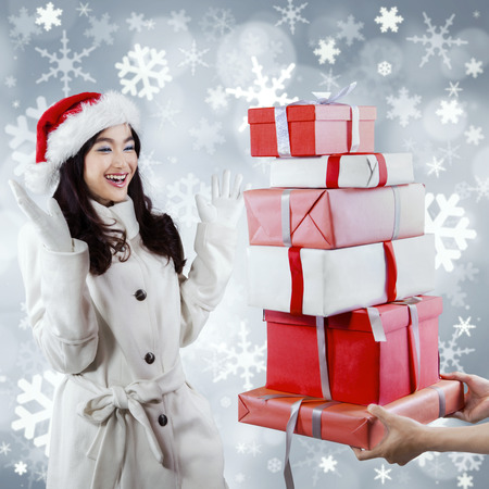 Portrait of surprised girl in winter clothes receive a pile of christmas gift box photo