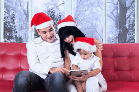 Little girl wither her parents wearing christmas hat and using a digital tablet on sofa in winter day photo