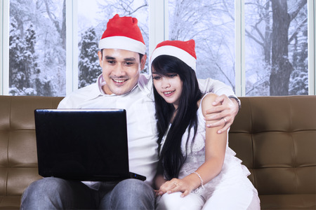 Portrait of happy couple sitting on sofa while wearing christmas hat and using laptop computer photo