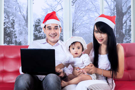 Portrait of beautiful little girl wearing christmas hat with her family using laptop in winter day photo