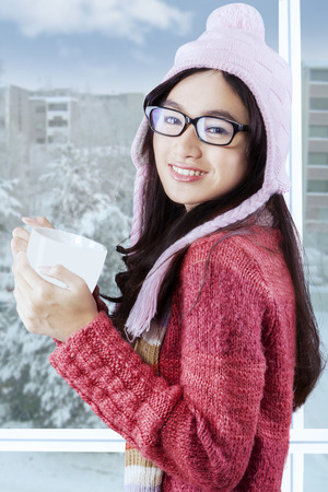 Portrait of friendly girl smiling on the camera while wearing winter clothes and enjoy a cup of hot drink at home photo