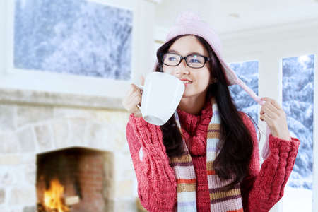 Portrait of beautiful girl wearing a knitted sweater and hat, drinking a cup of hot drink while standing indoor photo