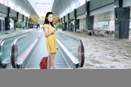 Young woman standing in airport corridor while carrying luggage and texting with mobilephone photo