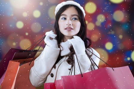 Portrait of pretty girl wearing winter jacket and holding shopping bags with defocused light background