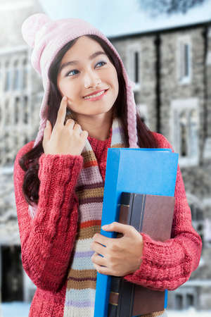 Attractive student wearing winter clothes and holding a book with folder outdoors photo