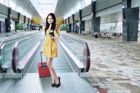 maletas de viaje: Retrato de joven asi�tico de pie en el pasillo del aeropuerto, mientras que el transporte de equipaje y que sostiene el pasaporte