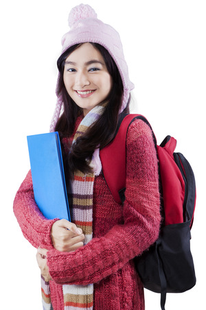 carying: Portrait of student smiling on the camera while wearing warm clothes and carying backpack, isolated on white
