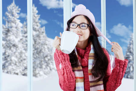 Attractive young asian girl wearing a knitted sweater, drinking a cup of hot coffee in winter day photo