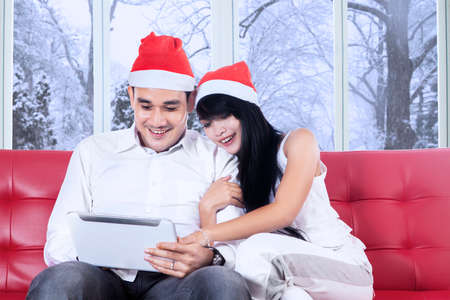 Portrait of young couple sitting on sofa while wearing christmas hat and using a digital tablet photo