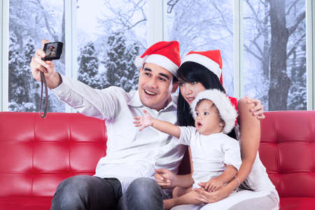Young asian family wearing santa hat and using a digital camera to take self portrait at home photo