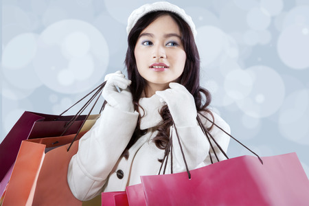 Beautiful girl in winter coat holding shopping bags with defocused light background