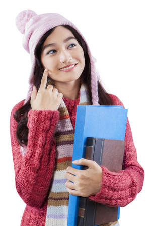 Portrait of asian student wearing knitted clothes and hat, standing in studio while holding a book and folder photo