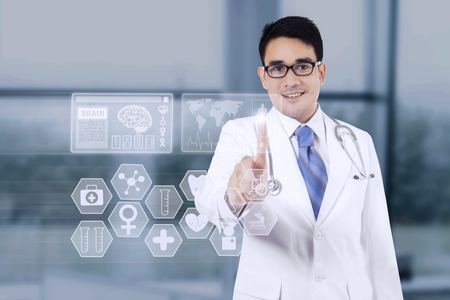 Portrait of young doctor pressing a button on the medical interface screen in the hospital