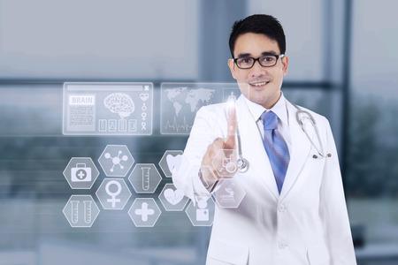 medicamentos: Retrato de joven m�dico presionando un bot�n en la pantalla de la interfaz de medicina en el hospital Foto de archivo