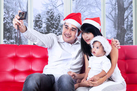 Asian father holding a digital camera to take picture with his family at home in christmas day photo