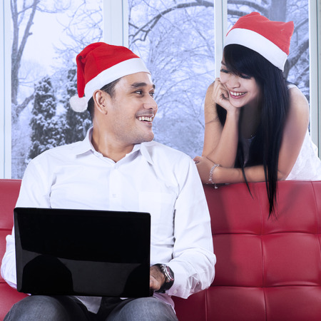 Portrait of young man in santa hat, sitting on sofa while using laptop and smiling at his wife on the back photo