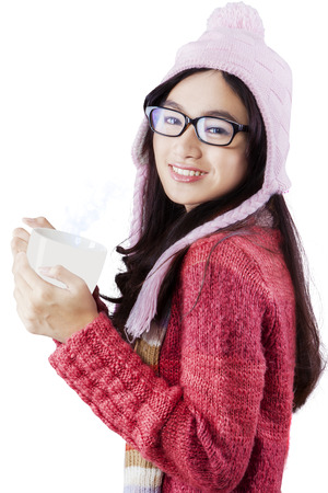 Young asian girl smiling on the camera while holding a cup of hot drink and wearing warm clothes, isolated over white background photo